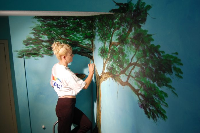 Local artist Kimberly Rideout painting a mural